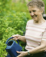 Community alarms client enjoying gardening